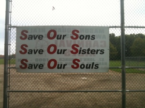 banner in city park: Save Our Sons, Save Our Sisters, Save Our Souls