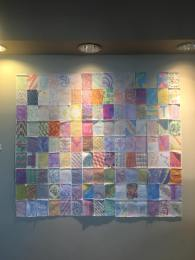 Quilt made of paper and crayon displayed on a wall.