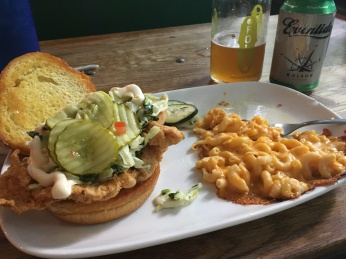 Fried chicken sandwich and macaroni and cheese on a plate.