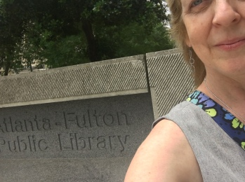Woman standing in front of sign for Atlanta-Fulton County Public Library.